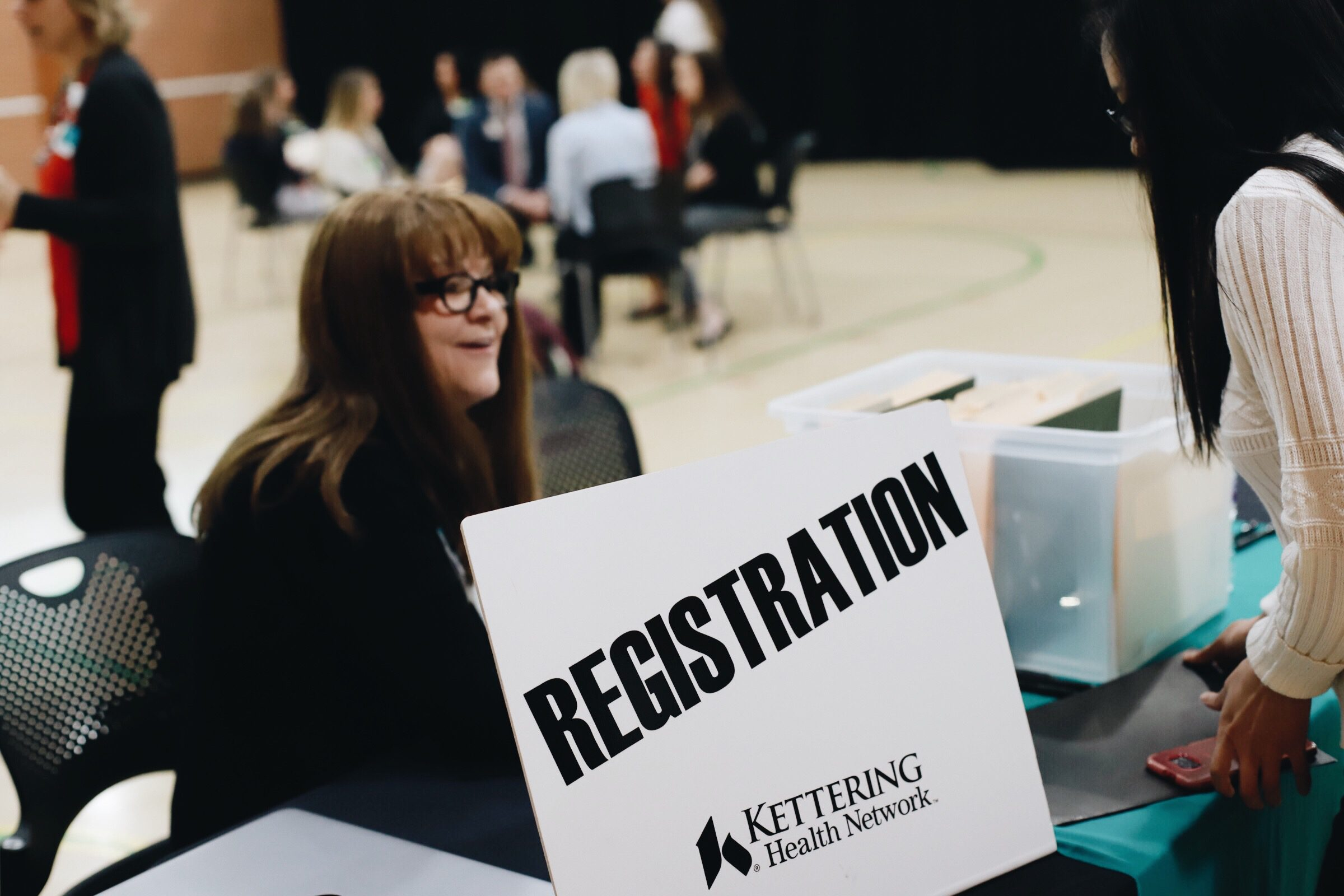 A student checks in at the registration table for Kettering College's BSN interview day with Kettering Health Network nursing managers